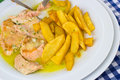 Salmon with curry sauce slices of and fried potatoes on white plate Royalty Free Stock Photography