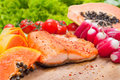 Salmon diet food grilled fish closeup with tomato and salad in background Royalty Free Stock Images