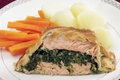 Salmon en croute meal fillet stuffed with a spinach mixture and encased in puff pastry served with boiled new potatoes and Royalty Free Stock Image
