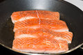 Salmon filé frying pan cooking in the Royalty Free Stock Photo