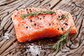 Salmon filet on a wooden carving board with spices macro shot Royalty Free Stock Photography