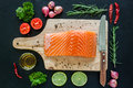 Salmon fillet on wooden board with garnish ready to cook lemon rosemary parsley and Stock Image