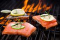 Salmon fillets on the grill with flames Royalty Free Stock Photography