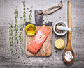 Salmon fillets with oil, lemon, salt and pepper, herbs on a cutting board on wooden rustic background top view close up