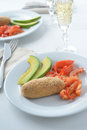 Salmon patty with vegetables baked red pepper tomato avocado and white wine Stock Photo
