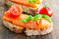 Salmon sandwich with basil and slice of fresh tomato Royalty Free Stock Image