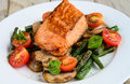 Salmon served with mushrooms asparagus cherry tomatoes pan fried and basil Stock Photos