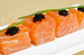 Salmon slices with black tobiko caviar and greens Stock Photography