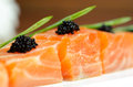 Salmon slices with black tobiko caviar and greens Royalty Free Stock Image