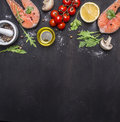 Salmon steak, butter, salt and pepper, lemon and cherry tomatoes on wooden rustic background top view border ,place for text Royalty Free Stock Photo