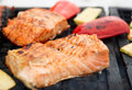 Salmon steaks being fried on grill with vegetables Stock Photos