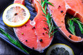 Salmon steaks in a grill pan with lemon, herbs and spices Royalty Free Stock Photo