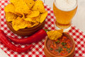 Salsa with tortilla chips and glass of beer chilli peppers Royalty Free Stock Image