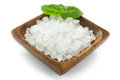 Salt crystals in wooden bowl and basil leaf closeup Royalty Free Stock Photo