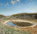 Salt lake in the desert steppe small round dries up dry semi with white residues along coast Stock Photo