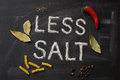 LESS SALT letters, spices and herbs on a blackboard