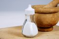 Salt with pestle and mortar cellar a wooden to the rear on a chopping board Stock Images