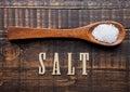 Salt on wooden spoon with letters below