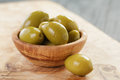 Salted giant green olives in olive bowl on wooden Royalty Free Stock Photo