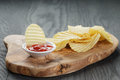 Salted potato ships with sauce on old wooden table Royalty Free Stock Photo