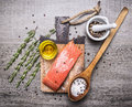 Salted salmon  fillet on a cutting board with delicious ingredients for cooking wooden rustic background top view Royalty Free Stock Photo