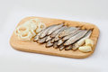 Salted sprats on cutting board with fresh onion Royalty Free Stock Images
