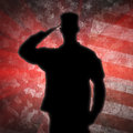 Saluting soldier s silhouette on an army camouflage background a green Royalty Free Stock Images