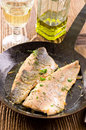 Salvelinus fillet fried with herbs ith as closeup in a wrought iron pan Stock Image