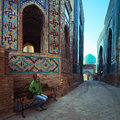 Samarkand young lady tourist sitting on a bench and enjoying oriental atmosphere of ancient complex of shah i zinda uzbekistan Stock Photography
