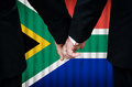Same sex marriage in south africa two gay men stand hand hand before a altar featuring an overlay of the flag colors of having Stock Image