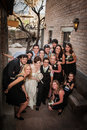 Same sex wedding party group from a sitting outside near brick wall Stock Photos