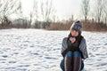 Sammanträde för ung kvinna utomhus i vinter och drickate Royaltyfri Fotografi