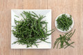 Samphire coastal vegetable on a white plate and bowl over oak wood background Royalty Free Stock Images