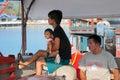 SAMUI, THAILAND - JANUARY 20,2011: Two Thai men and a boy waitin