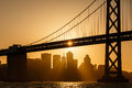 San francisco skyline at sunset framed by bay bridge silhouettes buildings as sailboat glides under span of Stock Image