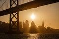 San francisco skyline at sunset silhouettes buildings as sailboat glides under bay bridge Stock Photography