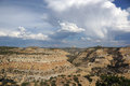 San rafael swell mountain landscape with rain falling from the c clouds and space trees in distance in utah Stock Photos