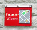 Sanctuary sign a red outside of a church reading welcome Stock Photography