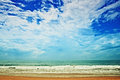 Sand beach, ocean and cloudy sky Royalty Free Stock Photo