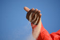 Sand in black male hand of an african american man red shirt running through his fingers front of blue sky background Stock Image