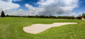 Sand bunker on golf course with perfect green grass Royalty Free Stock Photo