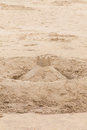 Sand castle with turrets on top made by children at the seaside on the beach with a central cone and around it a wall of Royalty Free Stock Photography