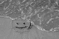On the sand drawn a smiley face and a wave washes, black and white Royalty Free Stock Photo