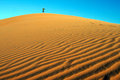Sand dune figure of a man on top of a Royalty Free Stock Image