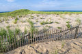 Sand dunes nobska beach a fence along the at on cape cod in massachusetts Stock Photos
