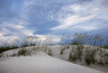 Sand dunes and stormy clouds enhanced by sea oats swaying the breeze Stock Photos