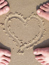 Sand heart with lovers foot Royalty Free Stock Image
