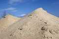 Sand mound yellow gravel against blue sky Stock Photo