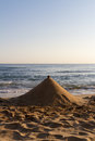 Sand pyramid structure on a beach with the ocean in the background Stock Photography