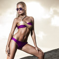 Sand rocks young lady in bikini standing on Royalty Free Stock Images